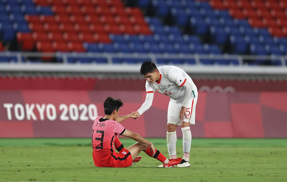 YOKOHAMA, JAPAN - JULY 31: Jinya Kim #13 of Team South Korea is consoled by Vladimir Lorona #6 of Team Mexico following defeat in the Men's Quarter Final match between Republic Of Korea and Mexico on day eight of the Tokyo 2020 Olympic Games at International Stadium Yokohama on July 31, 2021 in Yokohama, Kanagawa, Japan. (Photo by Francois Nel/Getty Images)
