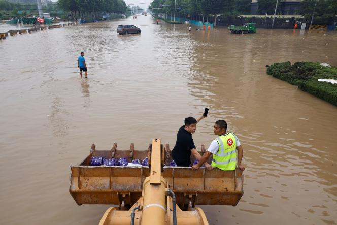 A front loader carries residents and water supplies through a flooded street in Zhengzhou, Henan province, China July 23, 2021.